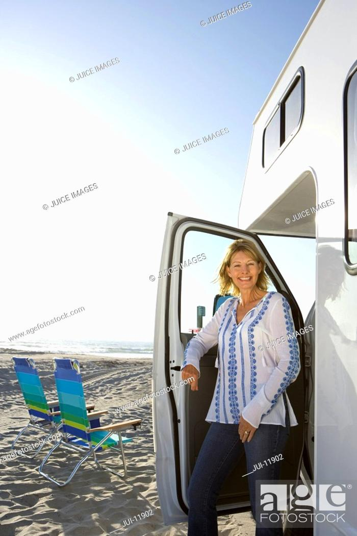 Stock Photo: Mature woman getting out of motor home on beach, smiling, portrait.