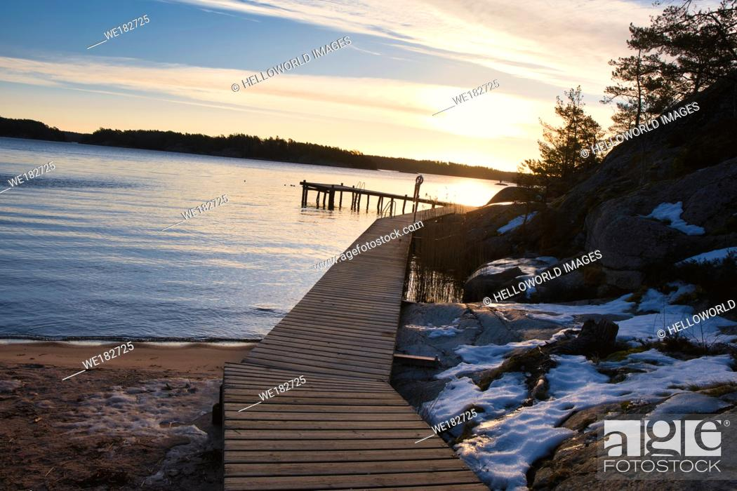 Stock Photo: Rustic wooden boardwalk and pier by the Baltic Sea in winter at dawn, Sweden, Scandinavia.