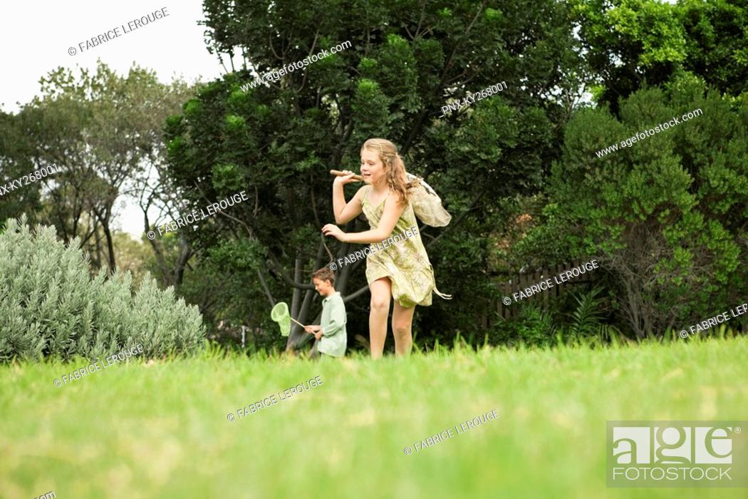 Stock Photo: Girl and a boy playing with butterfly nets in a garden.
