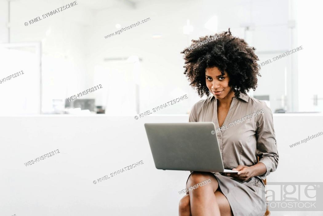 Stock Photo: Young woman using laptop in office.