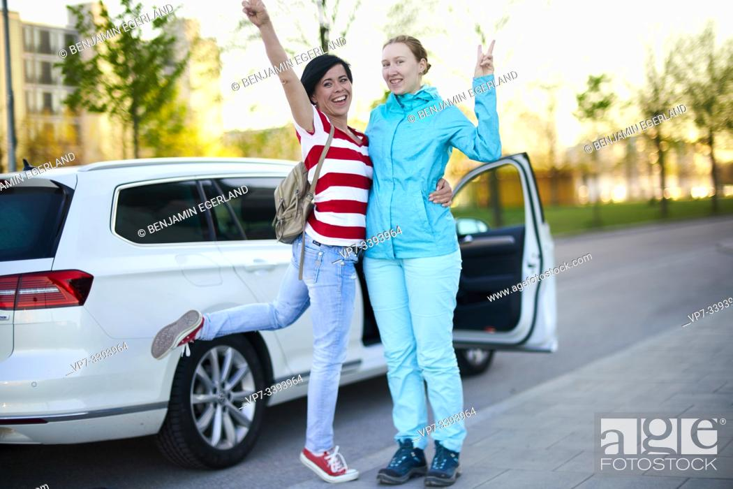 Stock Photo: two adventurous women in front of car with open door, ready to start adventure, in Munich, Germany.
