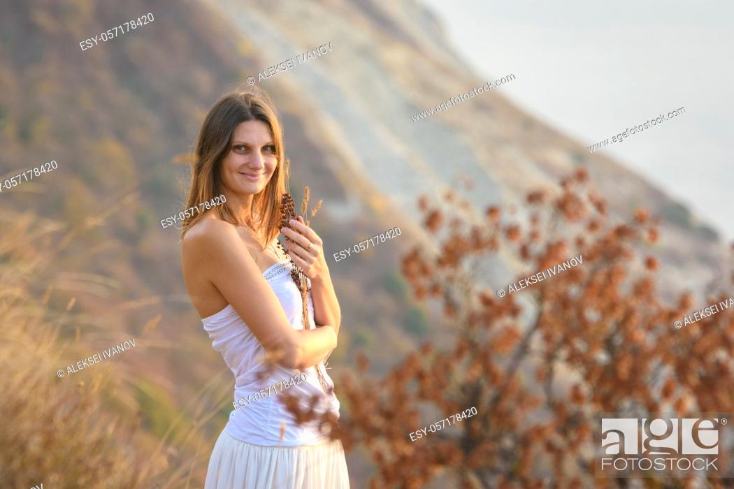 Stock Photo: Beautiful girl in a white dress on a background of mountains.
