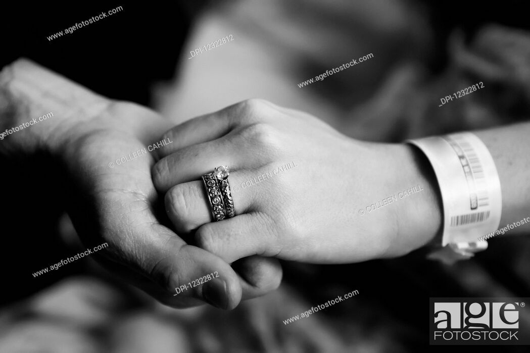 Stock Photo: A man and woman hold hands with a medical ID bracelet on the woman's wrist.