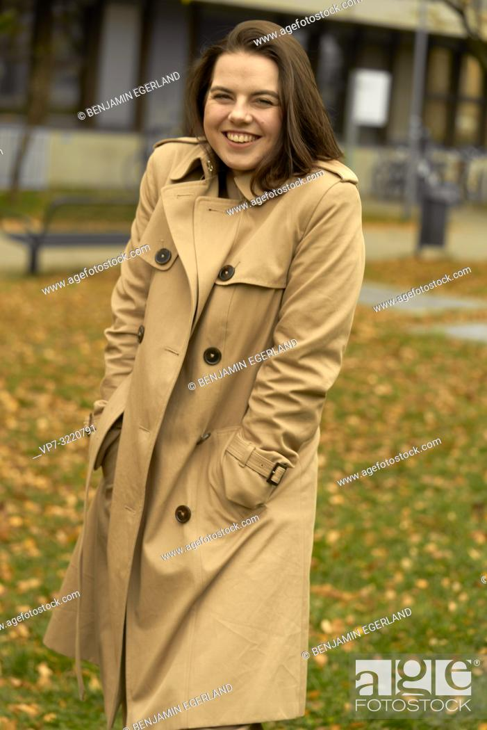 Stock Photo: young happy laughing woman outdoors in park during autumn season, wearing coat, candid emotion, pure happiness, in Munich, Bavaria, Germany.