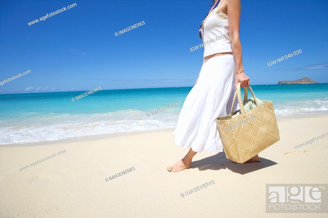 Stock Photo: Side view of a woman walking on beach.