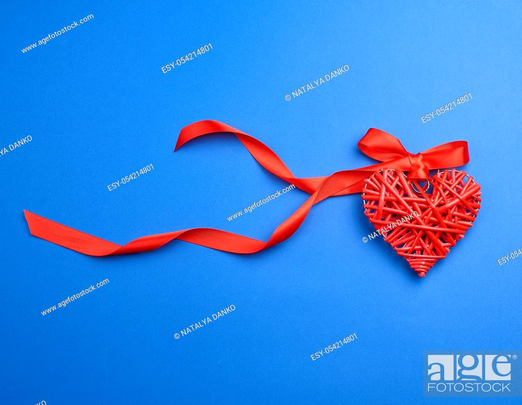 Stock Photo: red wicker decorative heart hanging on silk ribbon, blue festive background for Valentine's day.