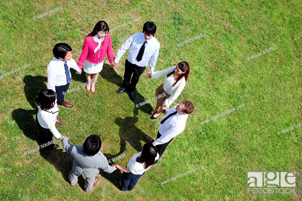 Stock Photo: Businesspeople in a circle in field, high angle.