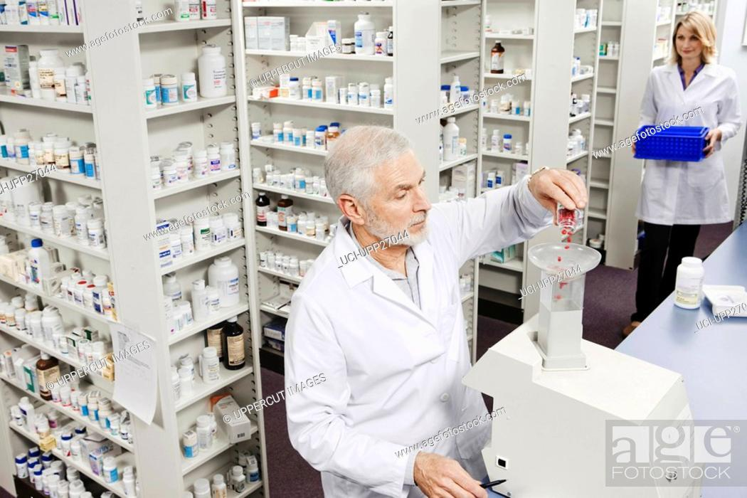 Stock Photo: Pharmacist pouring pills into counting machine.