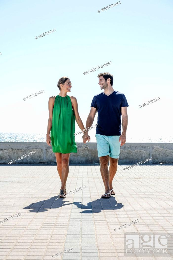 Stock Photo: Spain, Mid adult couple walking on pavement.