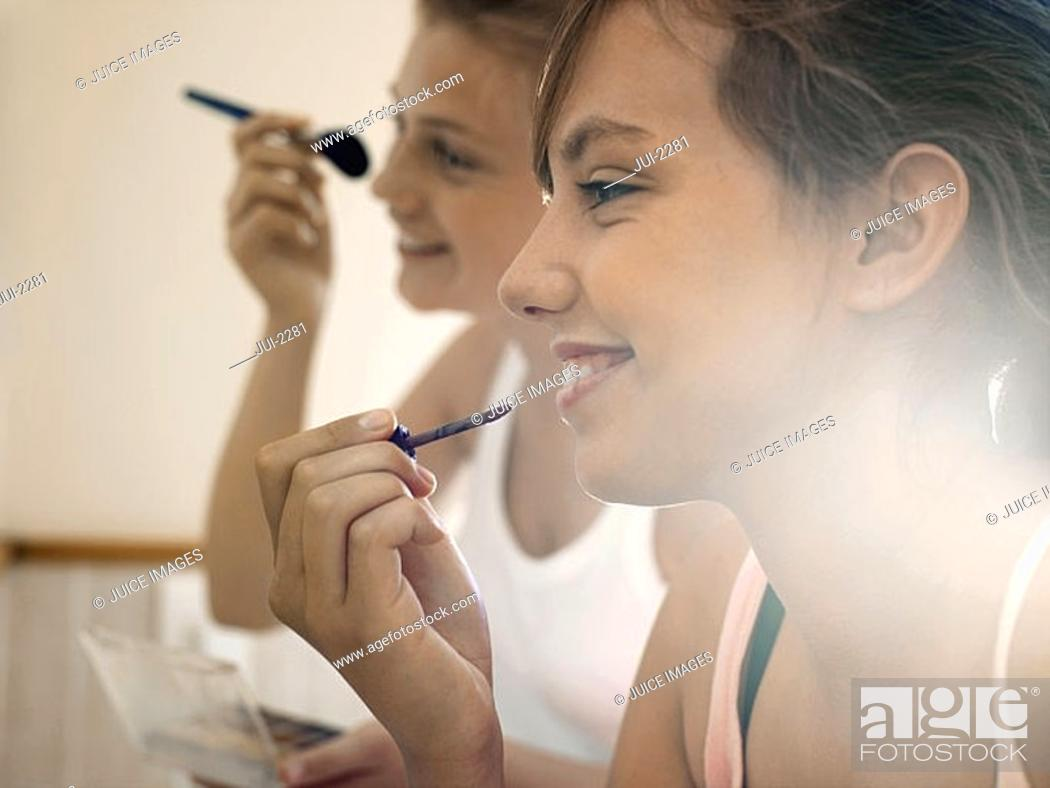 Stock Photo: Two teenage girls 15-17 applying make-up in bathroom, smiling, close-up, profile lens flare.