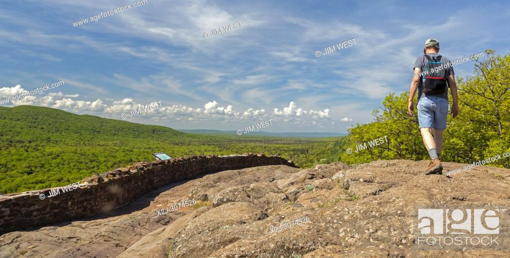 Stock Photo: Ontonagon, Michigan - 71 years old man hikes on the escarpment above Lake of the Clouds in Porcupine Mountains Wilderness State Park.