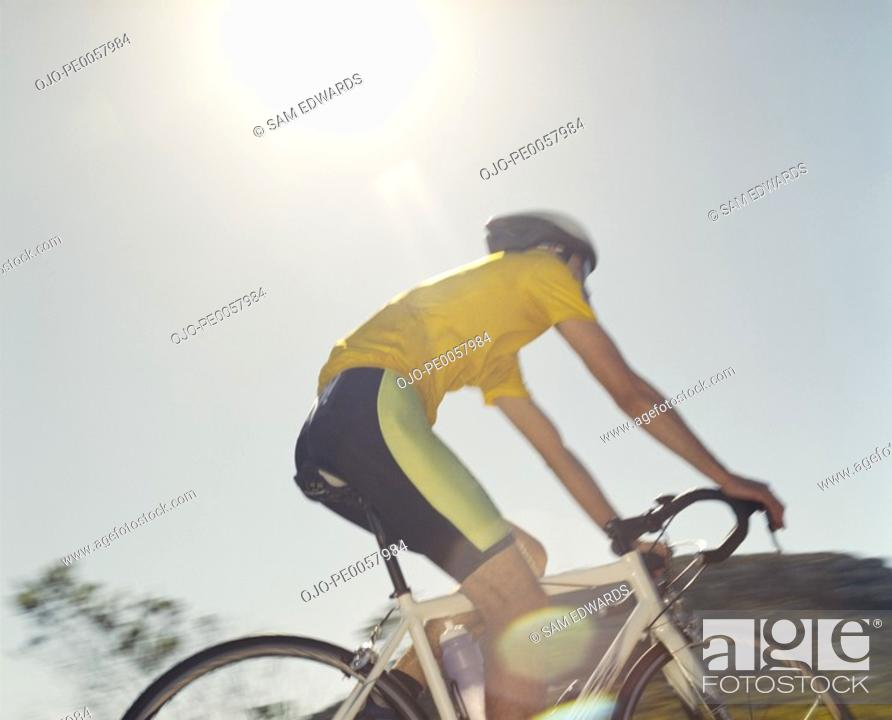Stock Photo: A man riding his bike on a sunny day.