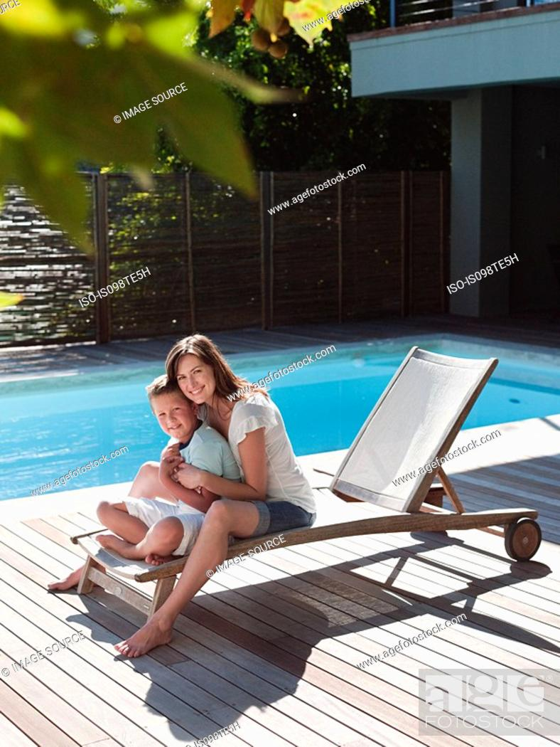 Stock Photo: Boy and mother on chair by pool.