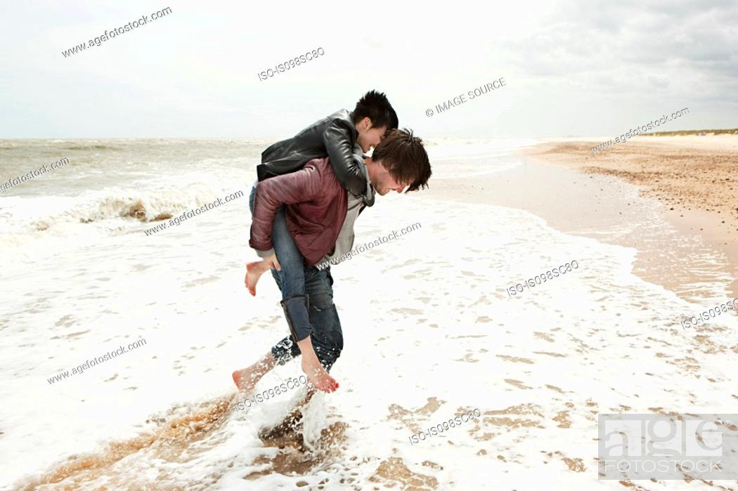 Stock Photo: Man giving girlfriend piggyback in the sea.