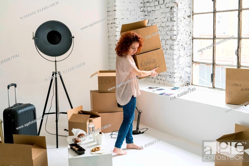 Stock Photo: Mid adult woman moving into industrial style apartment, carrying boxes.