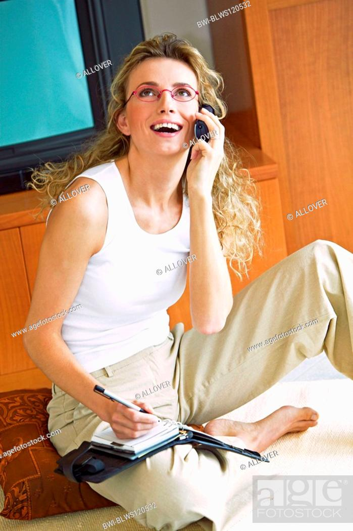 Stock Photo: woman at home with celluar phone and timer.