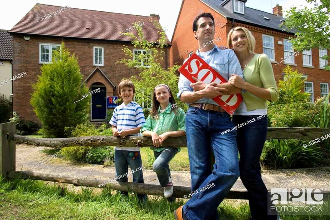 Stock Photo: 30's family with sold sign and house in background,.