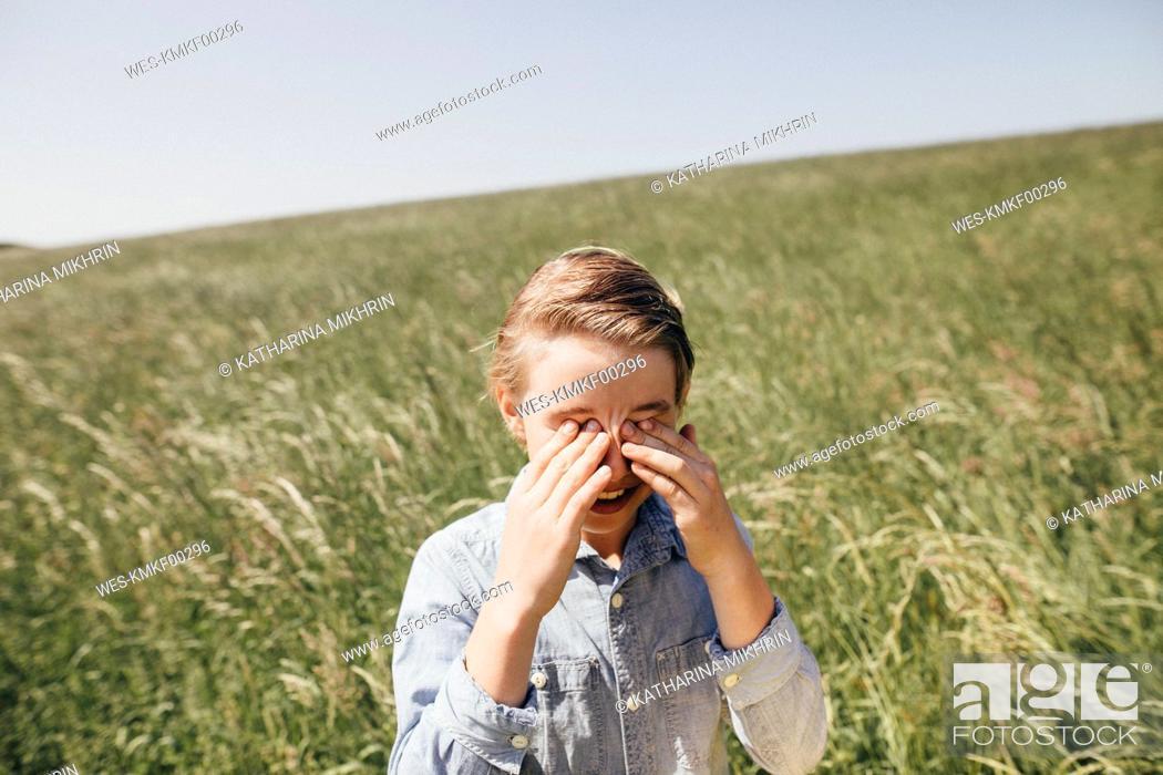 Stock Photo: Boy on a field rubbing his eyes.