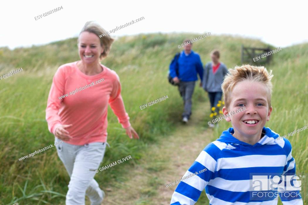 Stock Photo: Family of four running down the sanddunes onto the beach. They are wearing casual clothing and smiling.