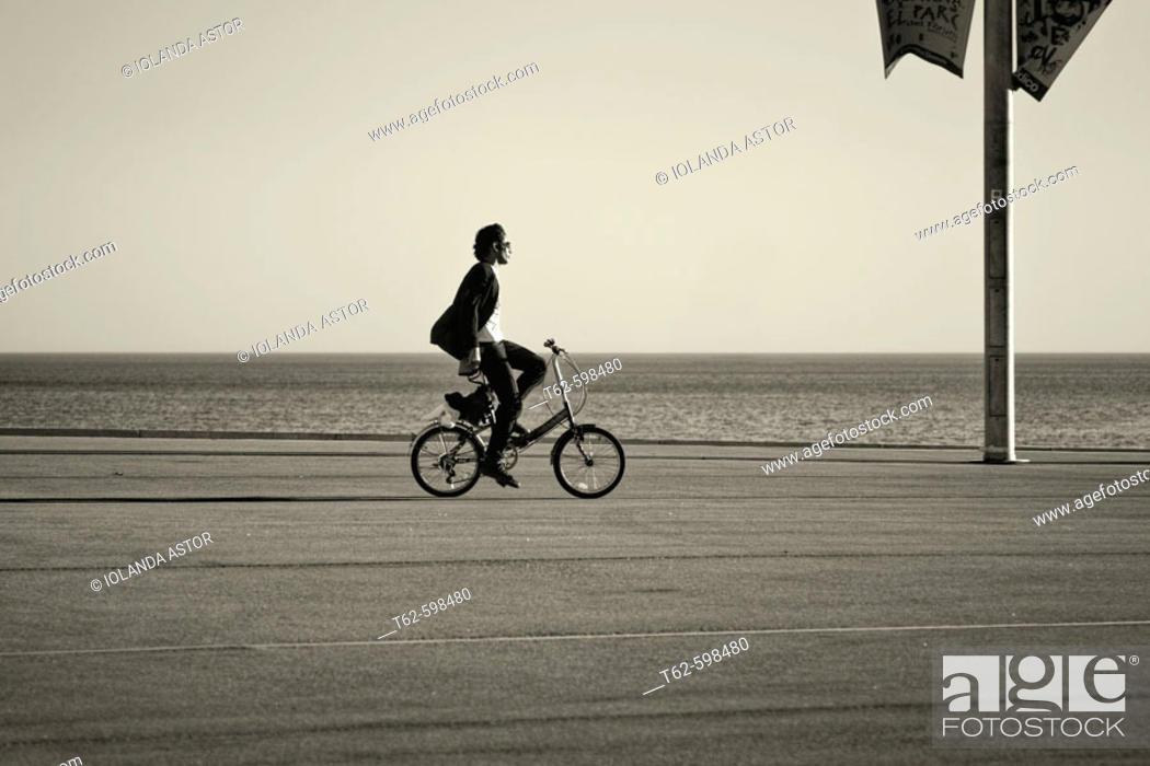 Stock Photo: Riding a bicycle on the Fórum de Barcelona. Catalonia. Spain.