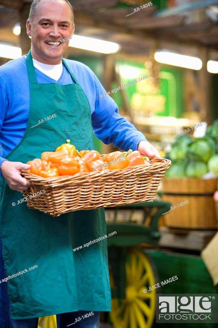 Stock Photo: Green grocer with basket of peppers, smiling, portrait.