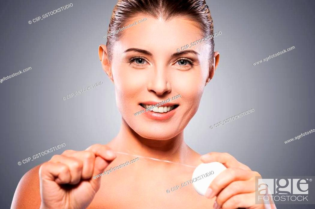 Stock Photo: Woman with dental floss. Beautiful mature woman holding dental floss and smiling at camera while standing against grey background.