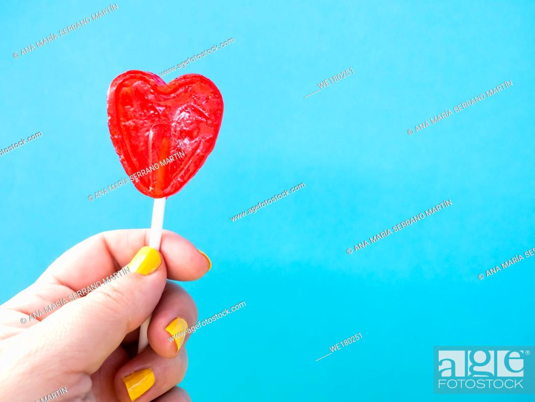 Stock Photo: A woman with yellow painted nails with a red lollipop in her hand and blue background.