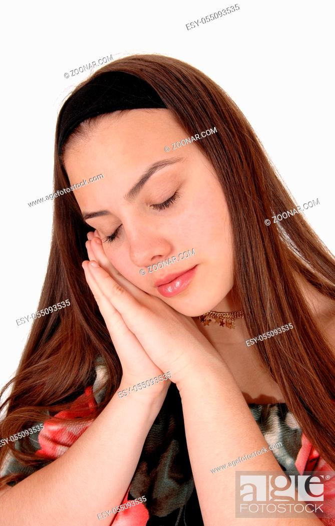 Stock Photo: A beautiful teenager girl holding both hands on her face and sleeping with her long brunette hair, isolated for white background.