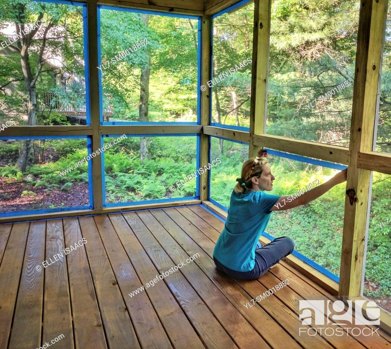 Stock Photo: Woman putting blue tape along screens in preparation for painting the posts of a screened porch in a DIY home improvement project.