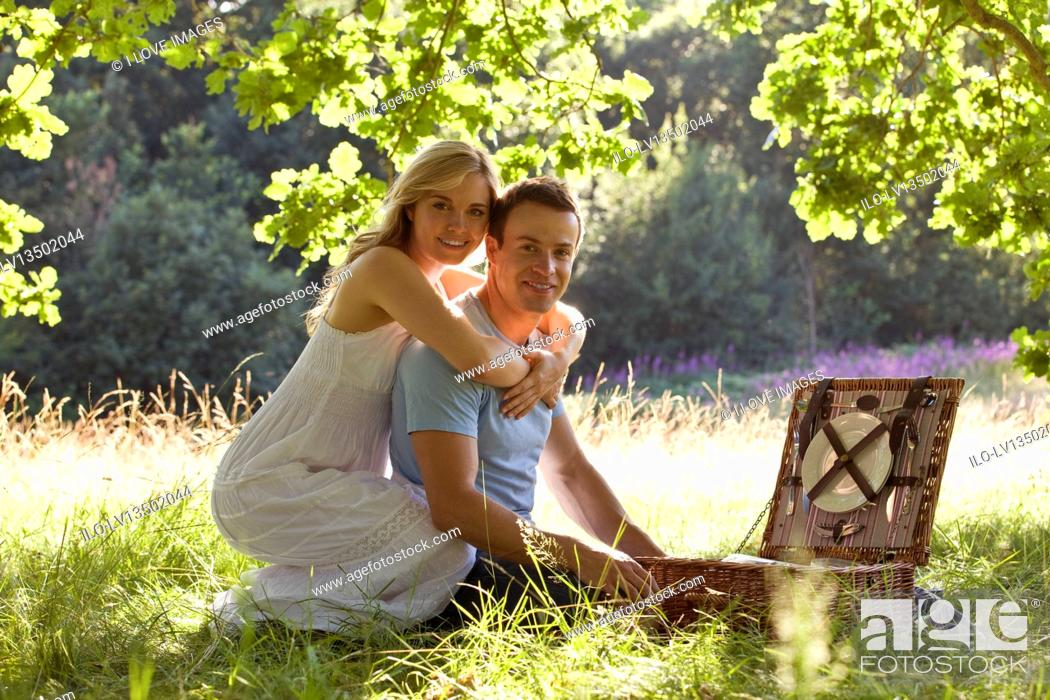 Stock Photo: A young couple having a picnic, embracing.