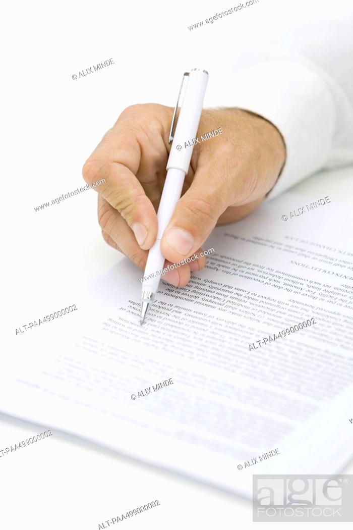 Stock Photo: Businessman reviewing contract with pen, cropped view of hand.