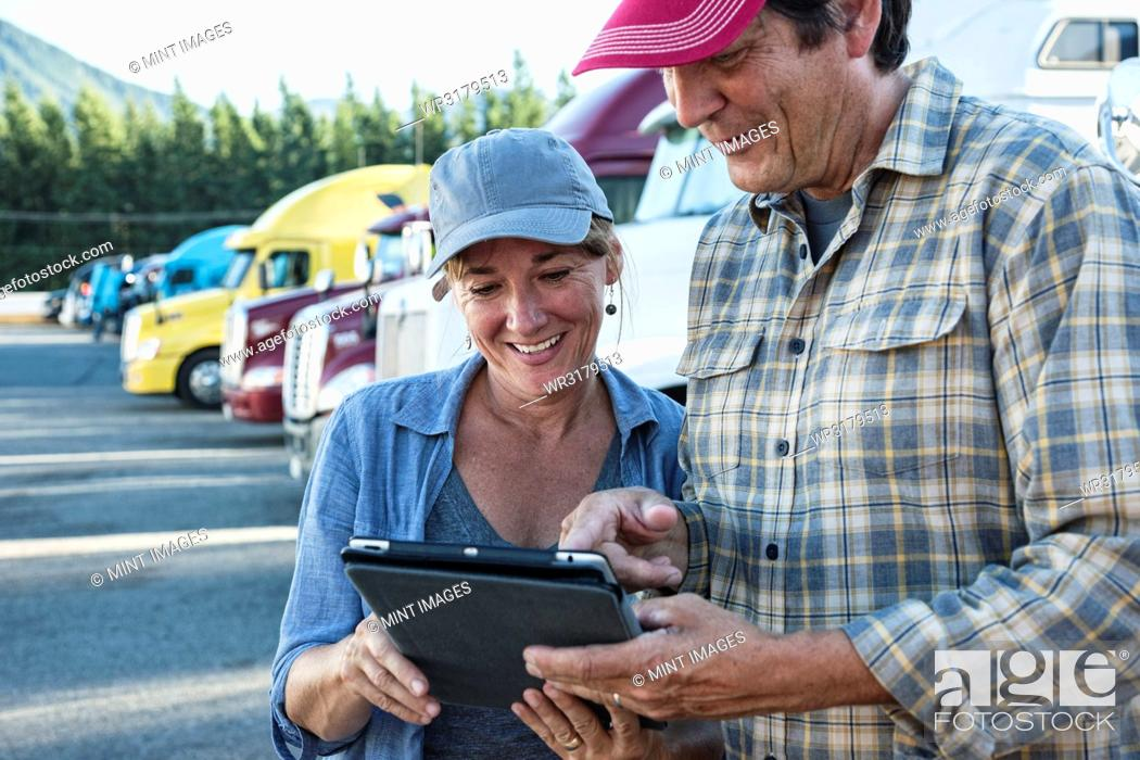 Stock Photo: Caucasian woman and man truck driving team working on their driving log in a truck stop parking lot.
