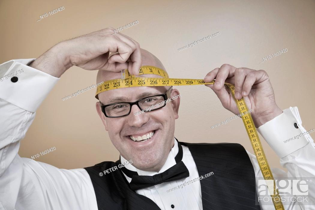 Stock Photo: Middle-age bald man measuring his head.