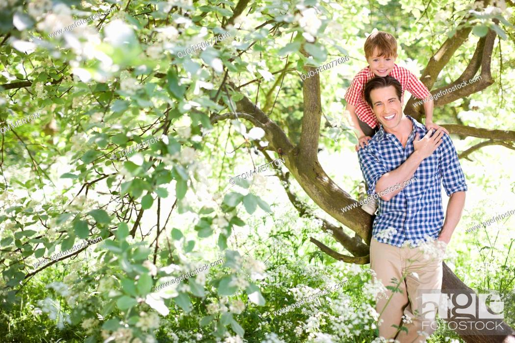 Stock Photo: Father playing with son on tree.
