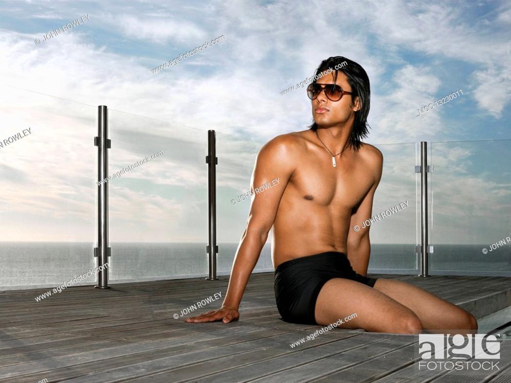 Stock Photo: Man in bathing suit sitting at poolside near ocean.