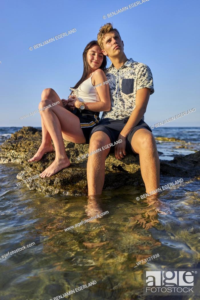 Photo de stock: Couple sitting on rock in sea, vacations, love. Chersonissos, Crete, Greece.