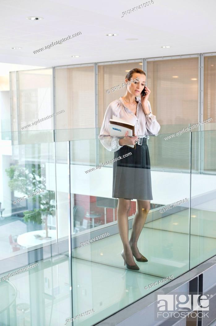 Stock Photo: Businesswoman talking on a mobile phone in an office corridor.
