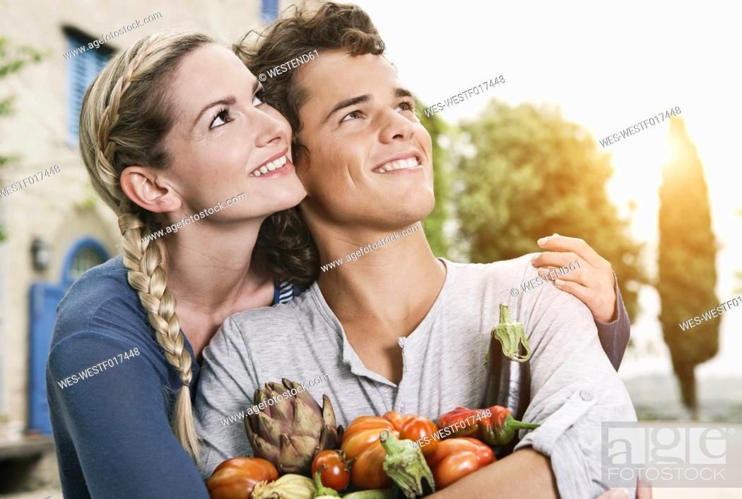 Stock Photo: Italy, Tuscany, Magliano, Young man and woman holding different vegetables, smiling.