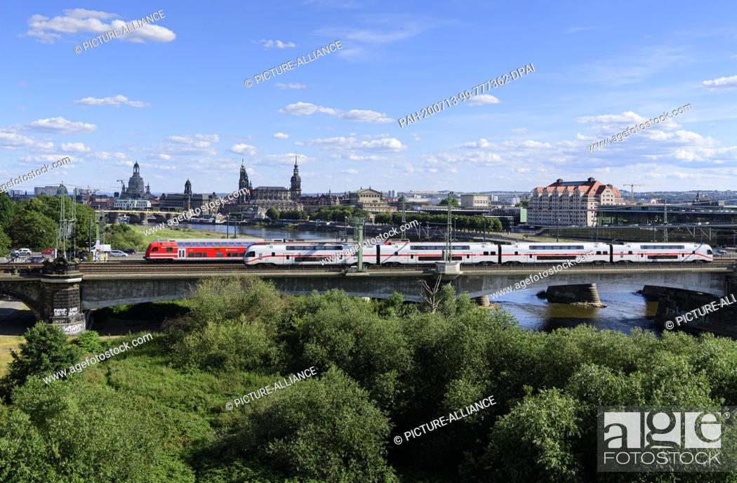 Stock Photo: 13 July 2020, Saxony, Dresden: An S-Bahn and an IC run in front of the historical old town scenery with the Frauenkirche (l-r), the Ständehaus, the Hofkirche.