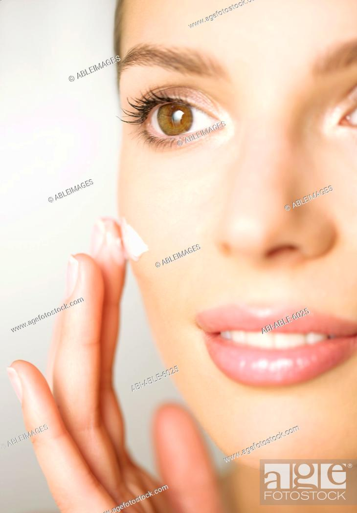 Stock Photo: Extreme close up of a woman applying cosmetic cream.