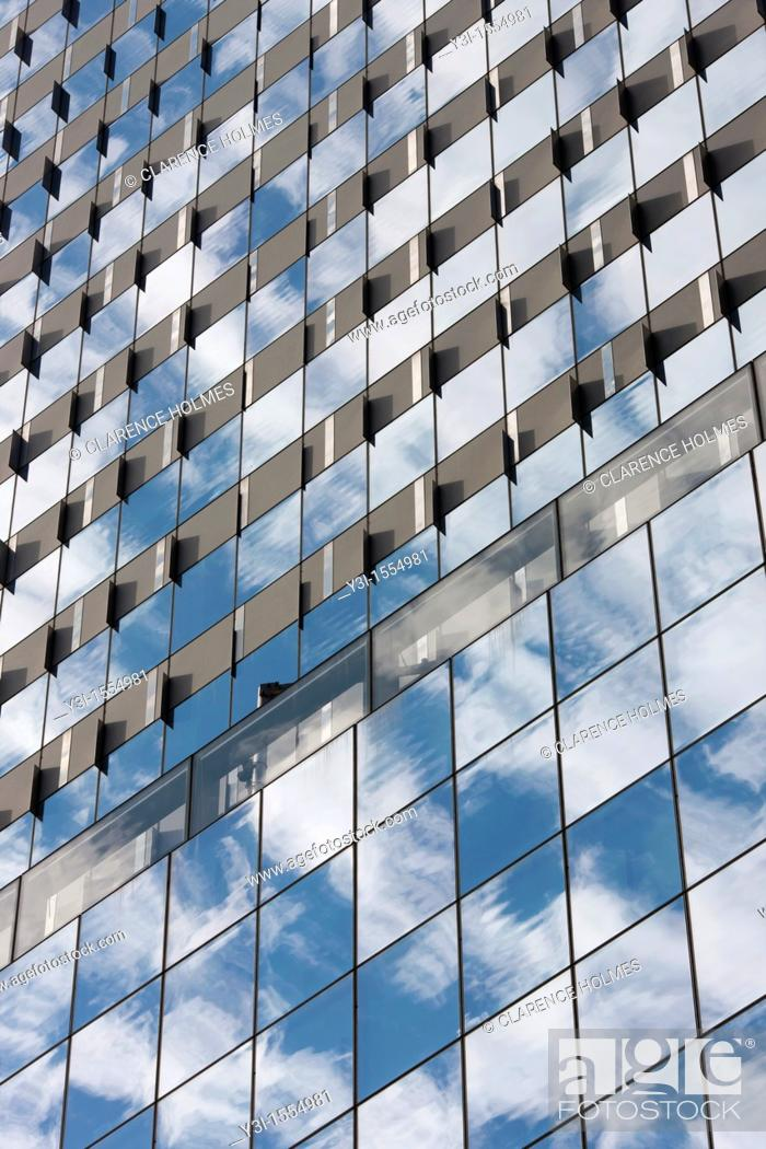 Stock Photo: The sky and clouds reflected in the windows of building facades in New York City, USA.