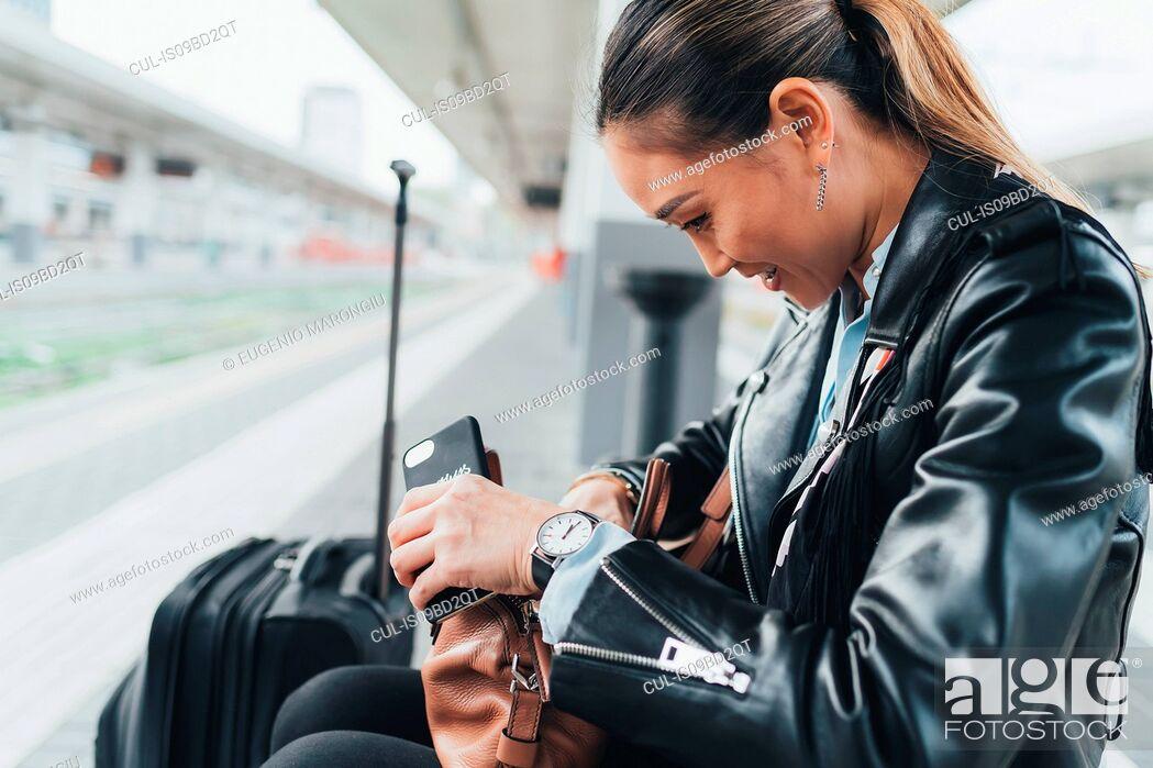 Stock Photo: Woman sitting on train platform, looking through handbag, suitcase beside her, holding smartphone.
