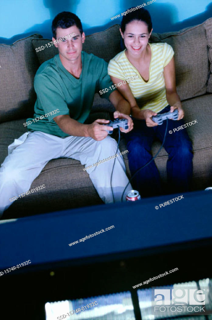 Stock Photo: Young couple sitting on a couch and playing a video game together.
