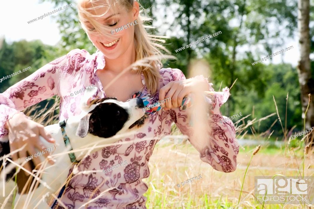 Stock Photo: Blond girl and a american bulldog in the park.