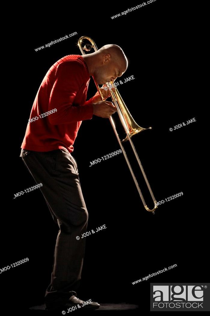 Stock Photo: Man Playing Trombone side view.