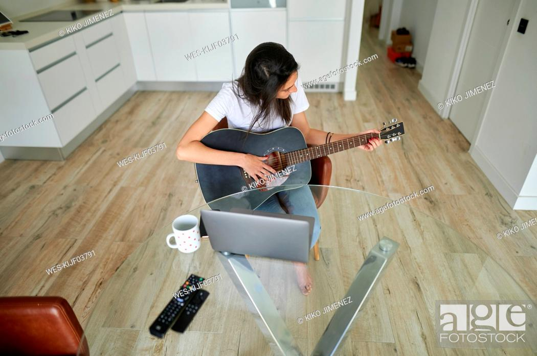 Stock Photo: Mid adult woman practicing guitar while sitting with laptop at home.