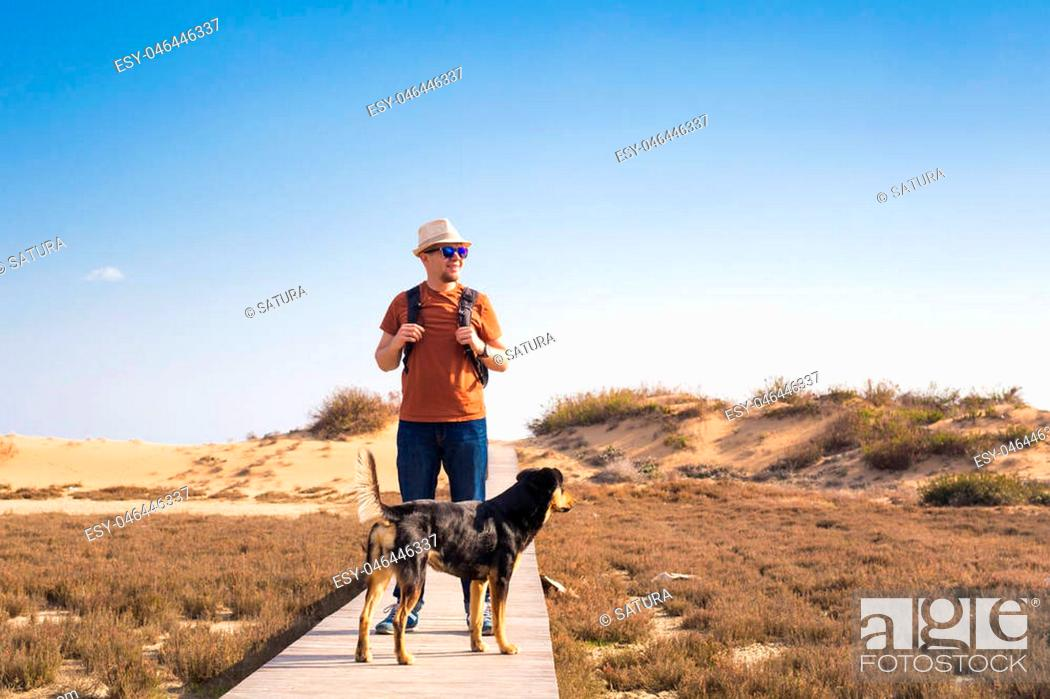 Imagen: Outdoors lifestyle image of travelling man with cute dog. Tourism concept.