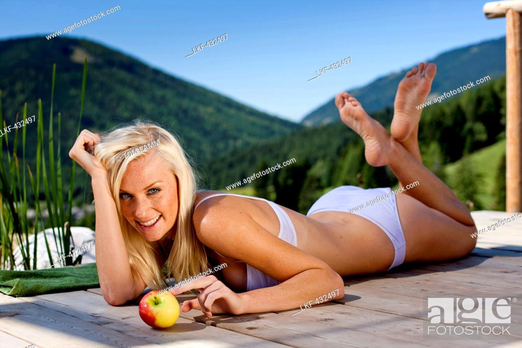 Stock Photo: Young woman with an apple lying on a jetty, Fladnitz an der Teichalm, Styria, Austria.