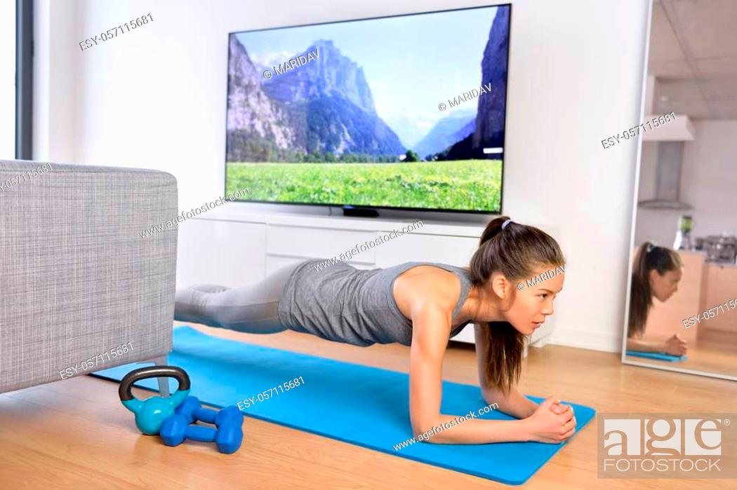 Photo de stock: Living room fitness workout - girl doing plank exercises to exercise core at home. Young Asian woman training muscles in front of the TV as part of a healthy.