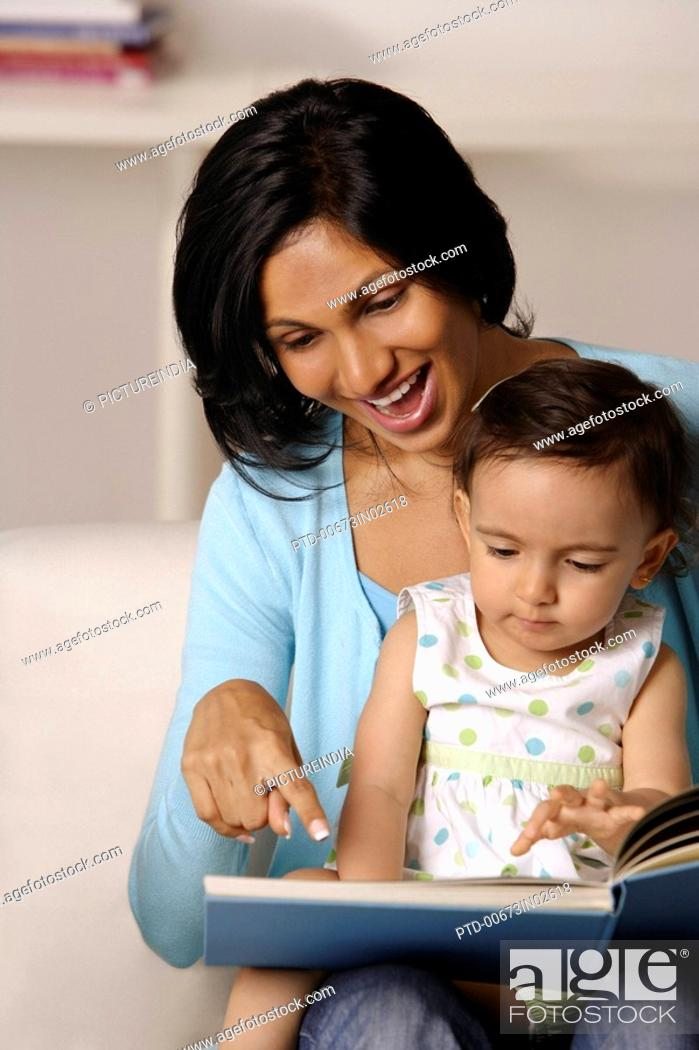 Stock Photo: woman flipping picture book with baby.